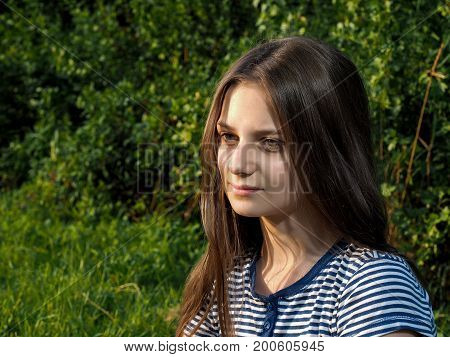Portrait of a beautiful young girl with long brown hair. Summer green grass nature