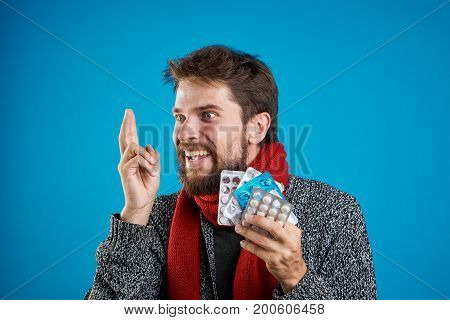 Man with a beard on a blue background holds a pack of pills, portrait, smile, illness, sick, flu.