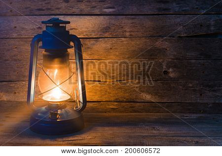 A kerosene lamp on an old wooden background with a burning fuse