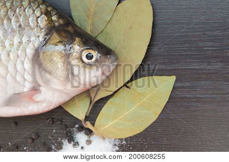Fresh Carp On The Black Board With The Bay Leaf And Pepper Salt.