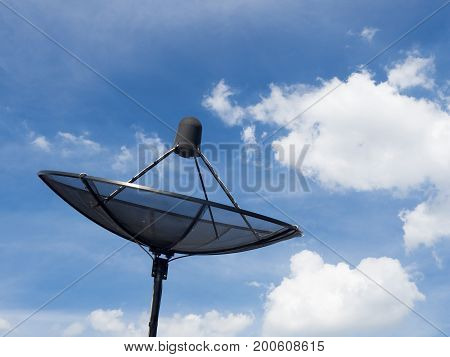 Black satellite dish or TV antennas install on the house roof on blue sky cloudy background.
