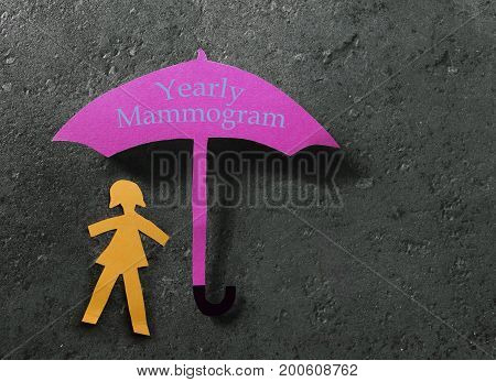 Paper woman under a pink Yearly Mammogram umbrella -- breast cancer prevention concept