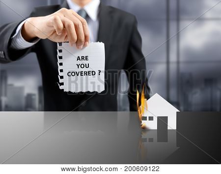 businessman present insurance concept with house on fire