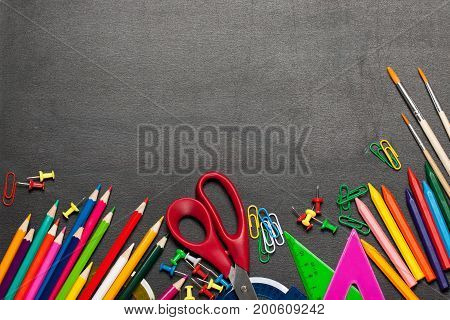 Colored school supplies on a dark background. The concept of returning to school education students etc.