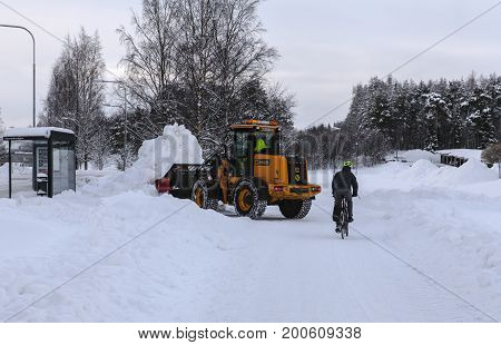UMEA, SWEDEN ON MARCH 03. A Wheel Loader, excavator in work with newly fallen snow on March 03, 2017 I Umea, Sweden. The digger plows the walkways to the buildings and bus stop. Editorial use.