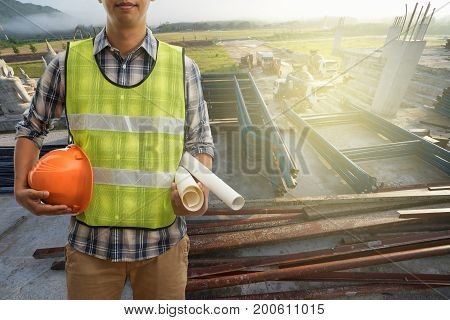 Engineer or Safety officer holding hard hat with blueprint on building construction site