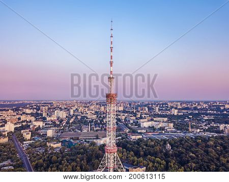 Television tower on city background bird's eye view urban sunset in the city.