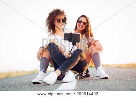 Skateboarder beautiful girl taking self portrait on smartphone