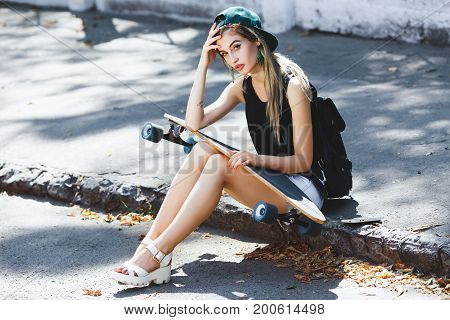 Nice Girl Sitting On The Pavement On The Street