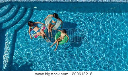 Aerial top view of family in swimming pool from above, happy mother and kids swim on inflatable ring donuts and have fun in water on family vacation