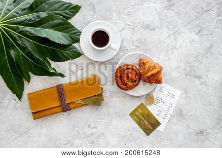 Pay restaurant bill. Bill, bank card, wallet, coins near cup of coffee and baking on light table top view.