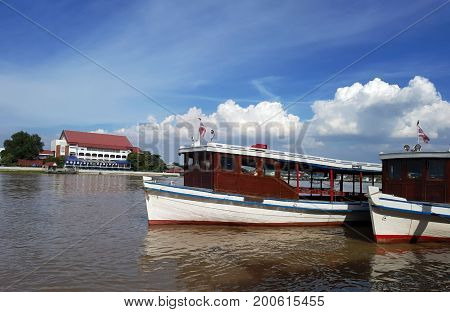Ferry station and ferry boat on river. Local ferry between two riversides is crossing river with many people on boardtourist passenger ferry boat at the dock leaving.