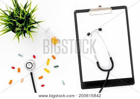 Doctor's workplace in clinic. Accessories. Clip pad and colored pills on white background top view.