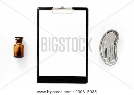 Doctor's accessories. Clip pad, pills nd cuvette with ampoulie on white background top view.