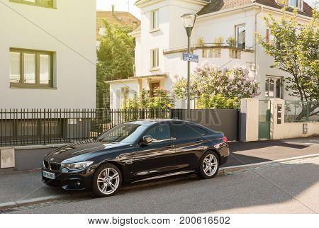 STRASBOURG FRANCE - APR 28 2017: Elegant executive black BMW German car parked on the Rue Gotfried in calm Strasbourg neighborhood.