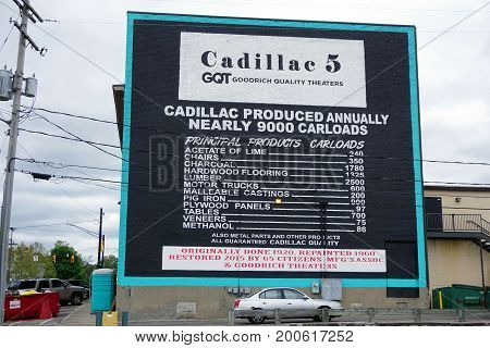 CADILLAC, MICHIGAN / UNITED STATES - MAY 31, 2017:  A large mural, painted on the back of the building of the historic Cadillac 5 Goodrich Quality Theater, in downtown Cadillac, lists the number of carloads of various products produced annually in Cadilla