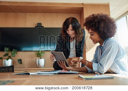 African businesswoman showing something on digital tablet to her female colleague while sitting at her desk. Professional employees discussing ideas of project on tablet pc.