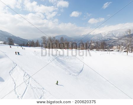 Sochi - March 28 2017: Happy people in bright clothes skiing and snowboarding in the high snow-capped mountains March 28 2017 Sochi Russia
