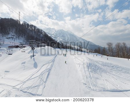 Sochi - March 28 2017: Happy people in bright clothes skiing in the high snow-capped mountains March 28 2017 Sochi Russia