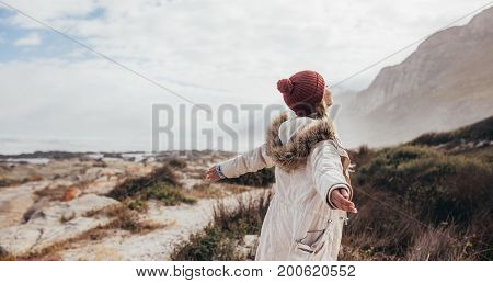 Outdoor shot of young woman on a winter day at the beach. Joyful female on a winter day with her arms outstretched along the seaside.