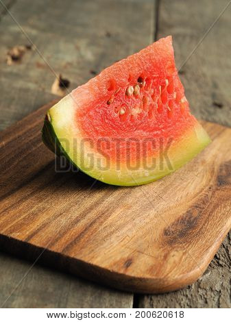 Piece of a water melon on a wooden cutting board
