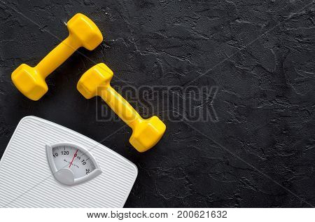 Fitness for losing weight. Bathroom scale and dumbbell on wooden background top view.