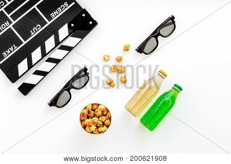 Food for watching film. Popcorn and soda near clapperboard, glasses on white background top view.