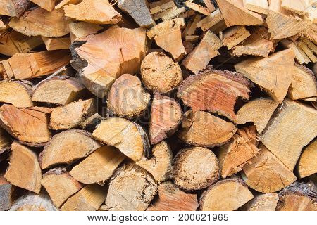 Natural wooden background texture closeup of chopped firewood. Firewood stacked and prepared for winter pile of wood logs
