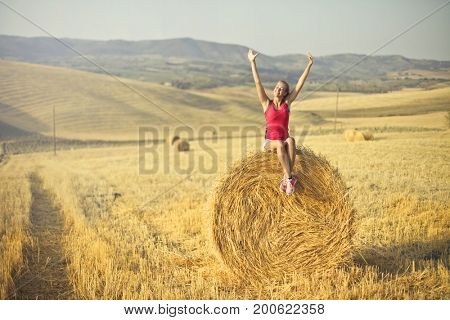 Joyful girl sitting on top of a hay bale in a grain field