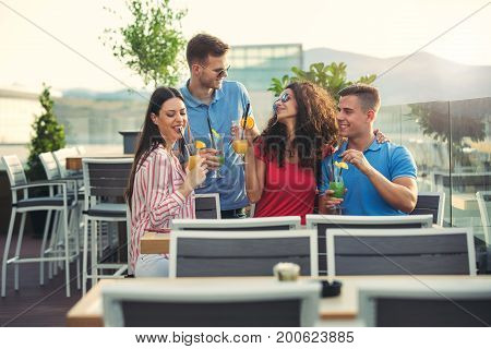 Friends having fun and drinking cocktails outdoor on a penthouse balcony