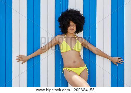 Afro American Girl In Yellow Bikini Standing With Arms Wide Open