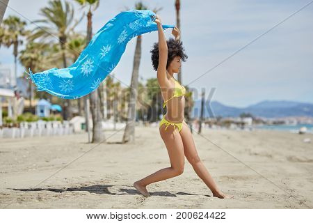 Afro American Woman Dancing On Beach Holding Shawl