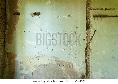 Interior house wall plaster with bullet holes and damage from shrapnel from grenade.