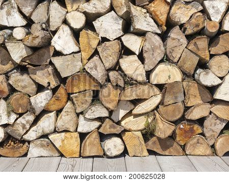 Wooden crushed birch dry firewood lie on top of each other on the street on the boards