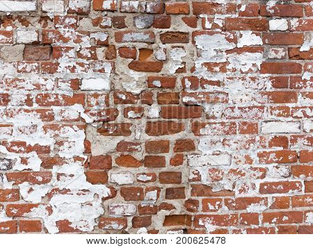 Old strong red brick wall with cracks with peeling white old paint