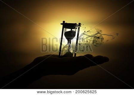 Silhouette hourglass is disintegrating on hand Pocket watch at last sunlight (Concept of wasting time)