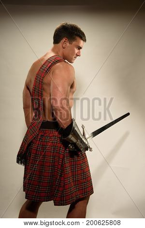 The handsome highlander prepares for battle with a sword