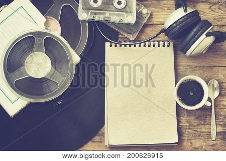 Retro music background vinyl records reel tape cassette headphones cup of coffee and notebook
