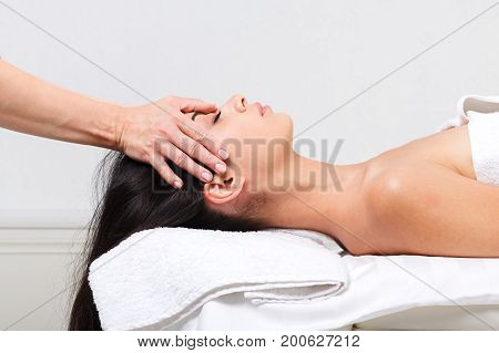 Head and face massage in spa. Female beautician work in wellness center. Professional massagist make relax healthy procedure to beautiful indian girl in cosmetology cabinet or beauty parlor.