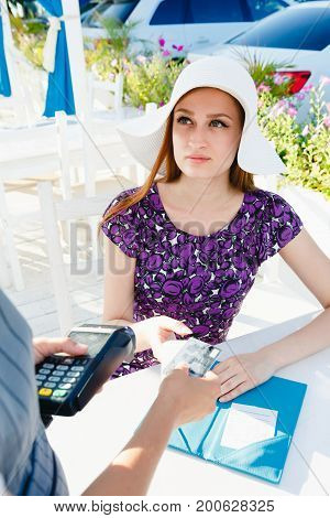 Anonymous server with payment terminal standing near young elegant customer and holding credit card in cafe.
