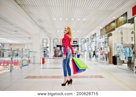 Portrait Of A Stunning Young Woman In Red Blouse, Ripped Casual Jeans And High Heels Posing With Sho