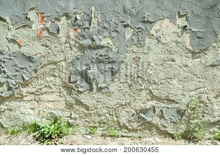 Bad foundation base of old house or building with damaged plaster