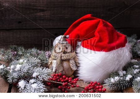 Christmas holiday composition with place for text. Santa hat decorative owl branches fur tree and red berries on aged wooden background. Selective focus.