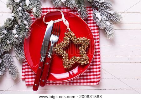 Christmas table setting. Red plate knife and fork napkin and christmas decorations in white and red colors on white wooden table. Selective focus.