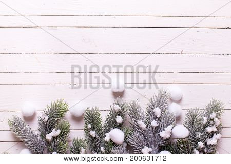 Border from branches fur tree on white wooden background. Decorative christmas composition. Top view. Selective focus. Place for text.