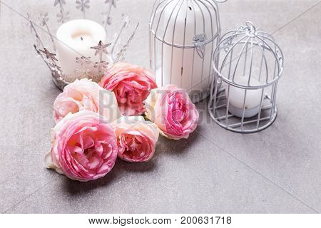 Postcard with fresh pink flowers roses and candles in candleholders on grey slate background. Selective focus. Place for text.