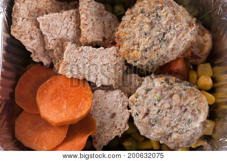 Healthy lunch in foil container. Healthy food take away and delivery. Slices of rusks, cutlets, corn, carrot, green pea, closeup