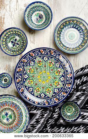 Ethnic Uzbek ceramic tableware. Decorative ceramic cups and plates with traditional uzbekistan ornament.