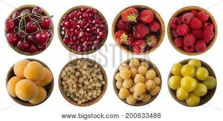 Yellow and red berries isolated on white background. Collage of different fruits and berries. Cherry strawberry pomegranate red currant raspberry apricot white currant yellow plum and yellow raspberry. Collection of fruits and berries in a bowl. Top view.