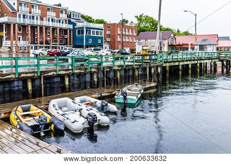 Castine USA - June 9 2017: Empty wooden marina harbor in small village in Maine during rain with boats and parking lot